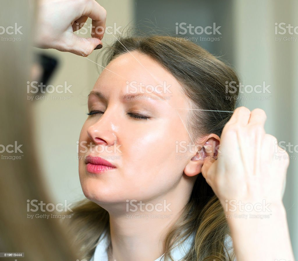 Make-up artist making eyebrow correction on model's face. stock photo