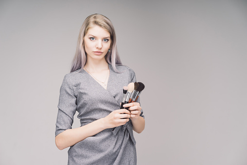 Makeup artist on gray background