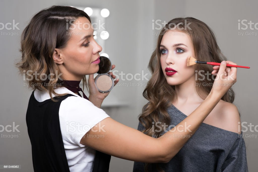 Makeup artist paints model in beauty studio stock photo
