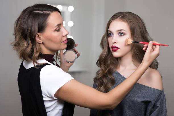 Makeup artist paints model in beauty studio stock photo