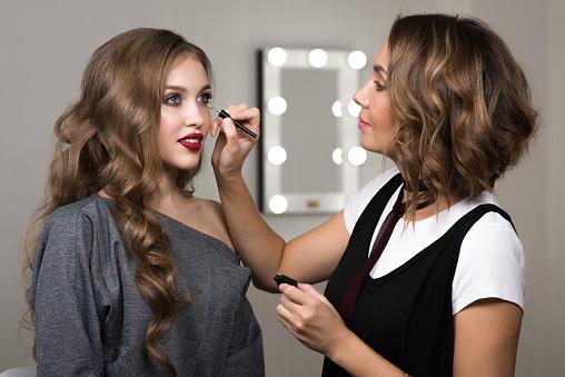 makeup artist paints model