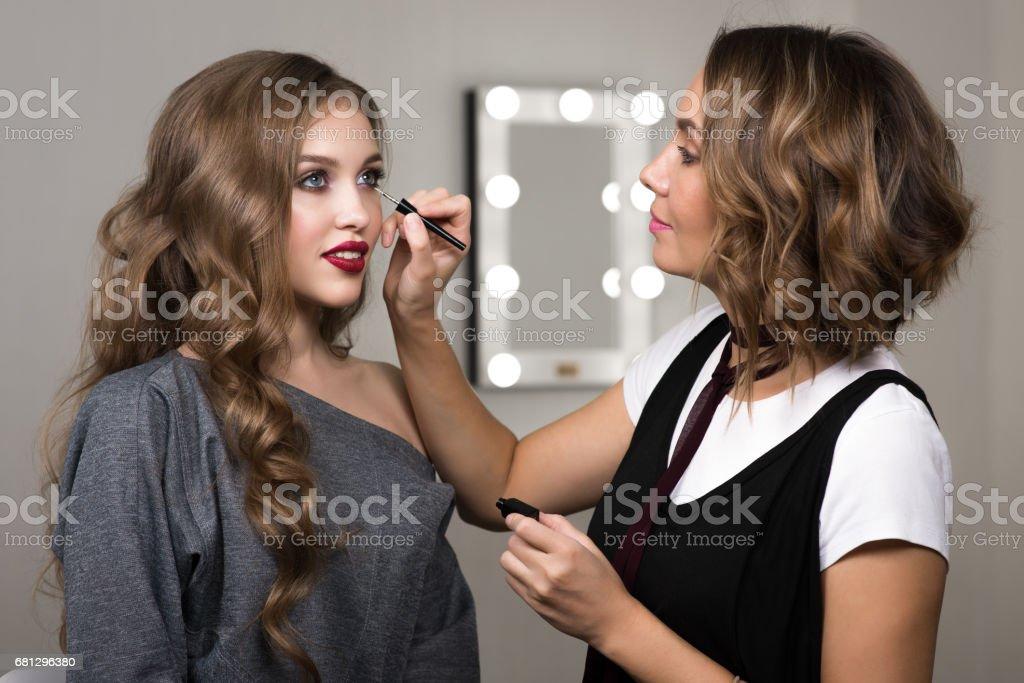 makeup artist paints model stock photo