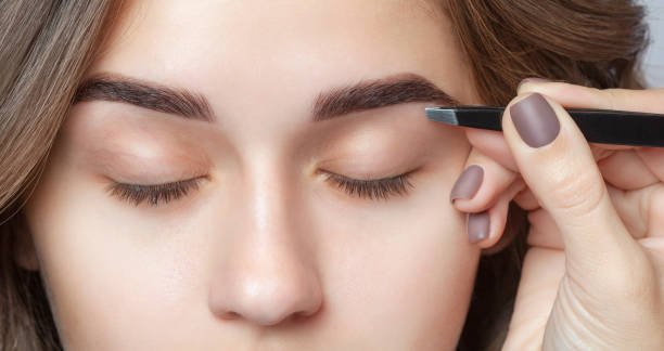 Make-up artist plucks eyebrows with tweezers to a woman. Beautiful thick eyebrows close up. Cosmetology concept stock photo