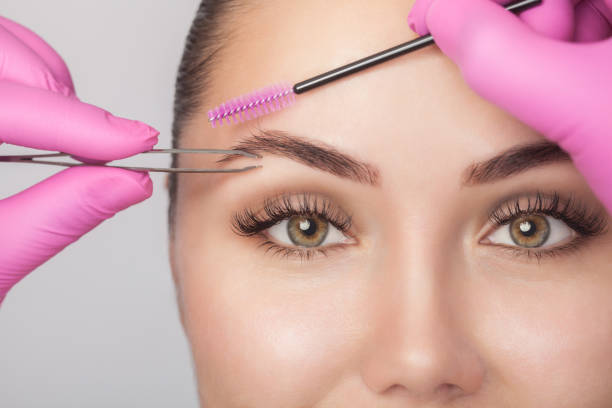 Makeup artist plucks eyebrows with tweezers to a woman before staining with henna. Cosmetology concept stock photo