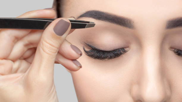 Make-up artist plucks eyebrows with tweezers to a woman with curly brown hair and nude make-up. Beautiful thick eyebrows close up. Professional makeup and cosmetology skin care. stock photo
