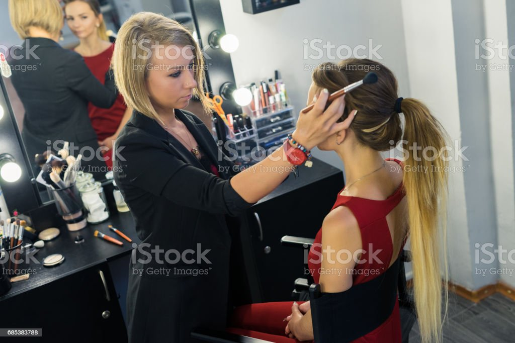 Make-up artist preparing for doing makeup to beautiful young girl foto de stock royalty-free