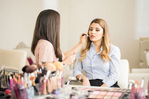 Makeup artist putting lipstick on a client