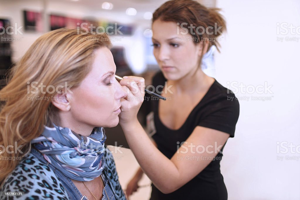 Make-up artist using a brush on a client royalty-free stock photo