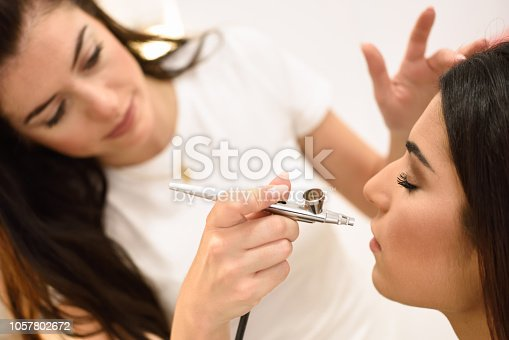 Make-up artist using aerograph making an airbrush make up to an African young woman in a beauty center. Beauty and Aesthetic concepts.