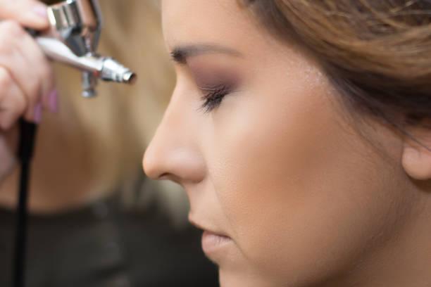 make-up-künstler mit airbrusher. - airbrush make up stock-fotos und bilder