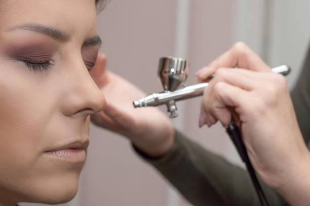 make-up-artist mit airbrusher. - airbrush make up stock-fotos und bilder