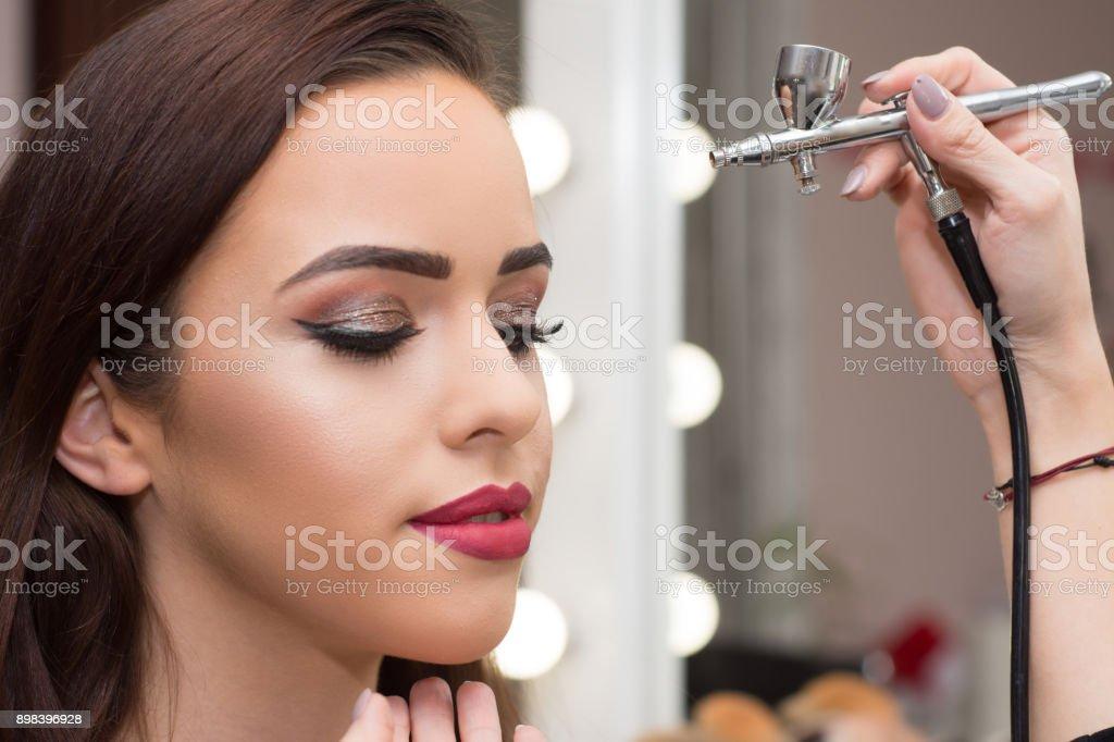 Makeup artist using airbrusher. stock photo