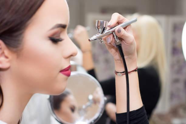 Makeup artist using airbrusher. Makeup artist using airbrusher. airbrush stock pictures, royalty-free photos & images