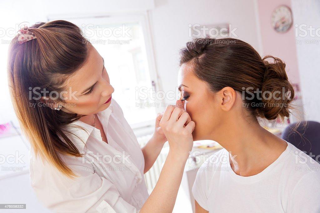 Make-up artist using artificial eyelashes stock photo