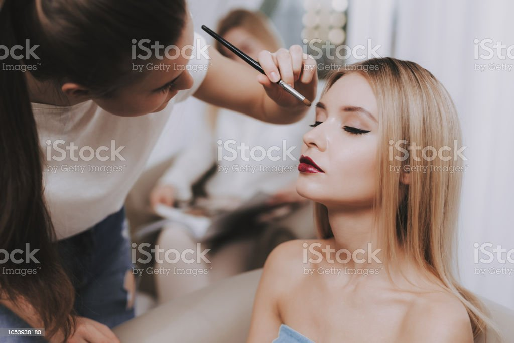 Makeup Artist with Brush in Hand and Blond Model. stock photo