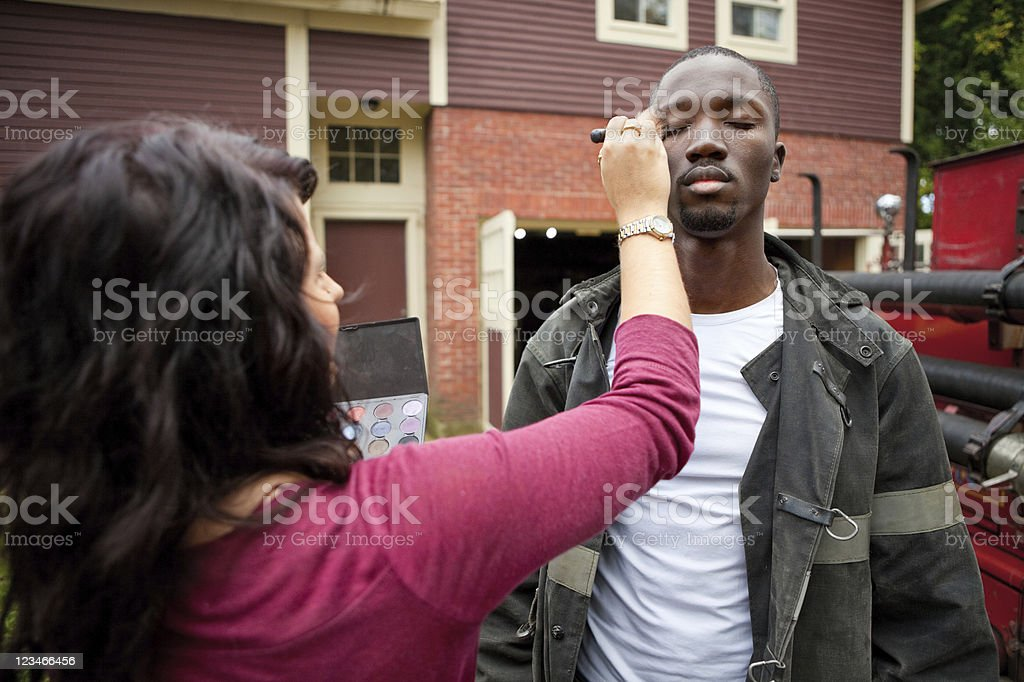Makeup artist working on actor model royalty-free stock photo