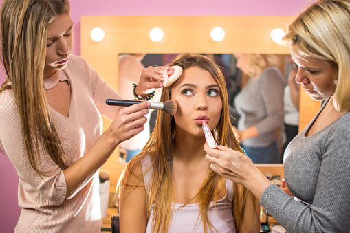 Makeup artists applying make-up on girl's face in beauty studio.