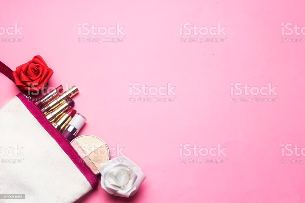 makeup bag contain a differents colorful lipsticks and face powder with red and white flowers on pink background - foto stock