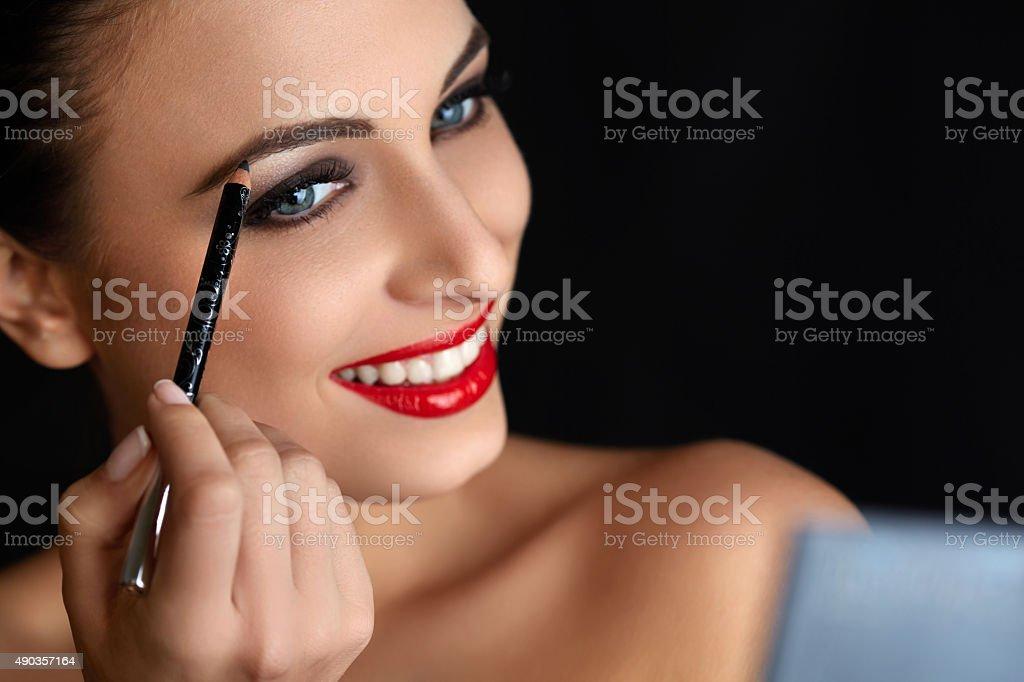Make-up. Beautiful Woman Doing Makeup. Eyebrow Pencil. Red Lips stock photo