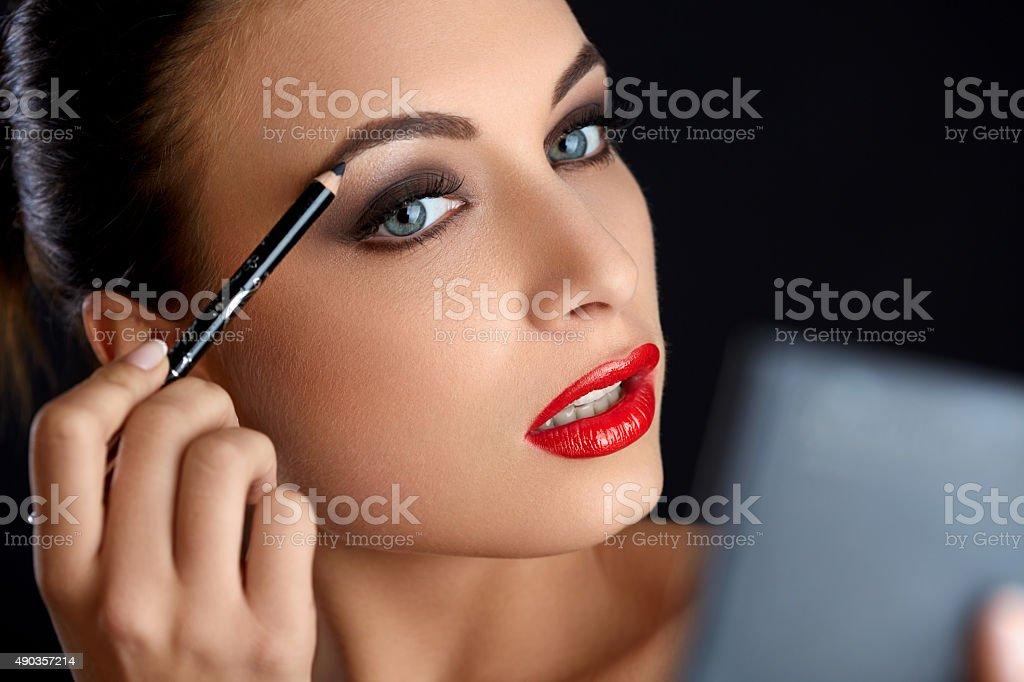 Make-up. Beautiful Woman Doing Makeup Eyebrow Pencil. Red Lips stock photo