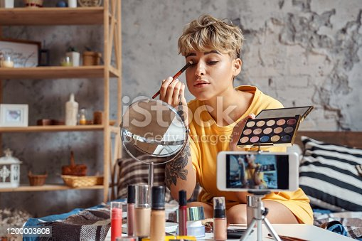 Young woman make-up blogger influencer sitting at stylish urban apartment recording video on smartphone camera looking at mirror applying eyeshadow concentrated