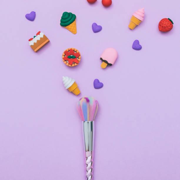 make-up pinsel unter die dessert-bonbons - make up torte stock-fotos und bilder