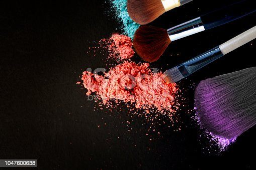 istock Makeup brushes and eye shadows on black background 1047600638