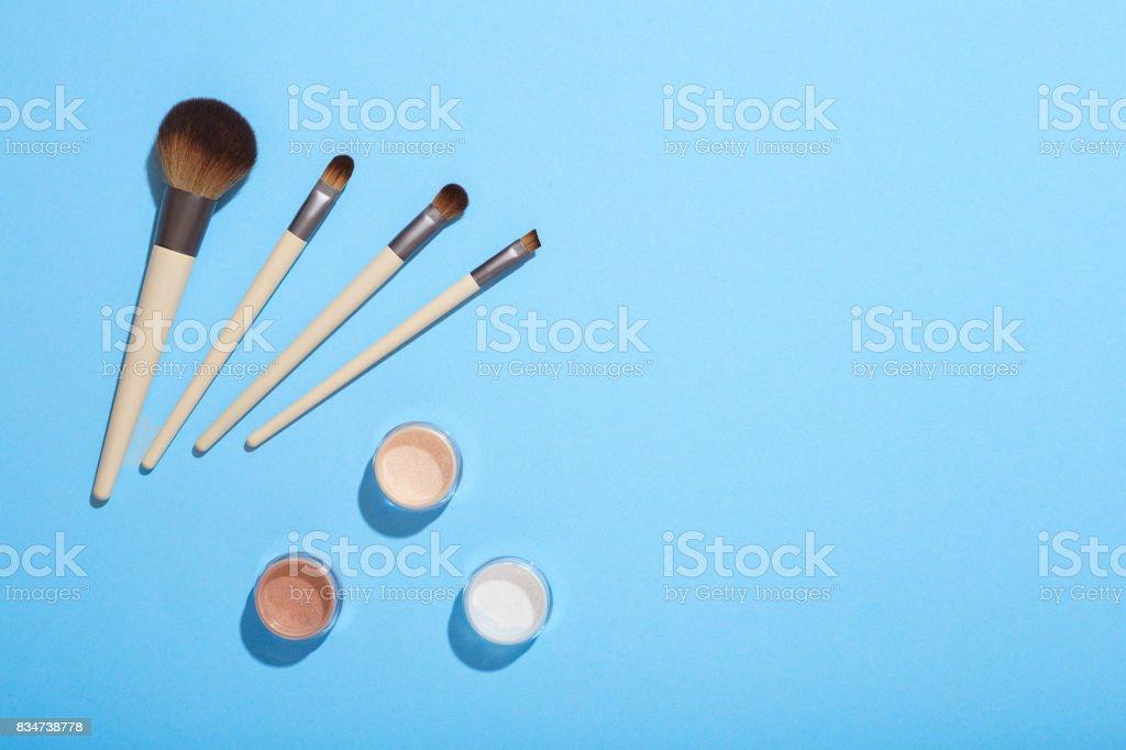Pinceles de maquillaje y sombras sobre fondo azul - foto de stock