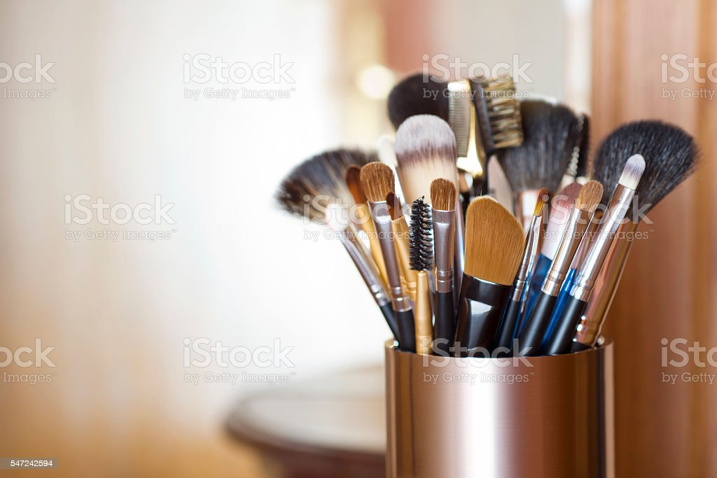 Makeup brushes in metal stand over blurred abstract room background stock photo