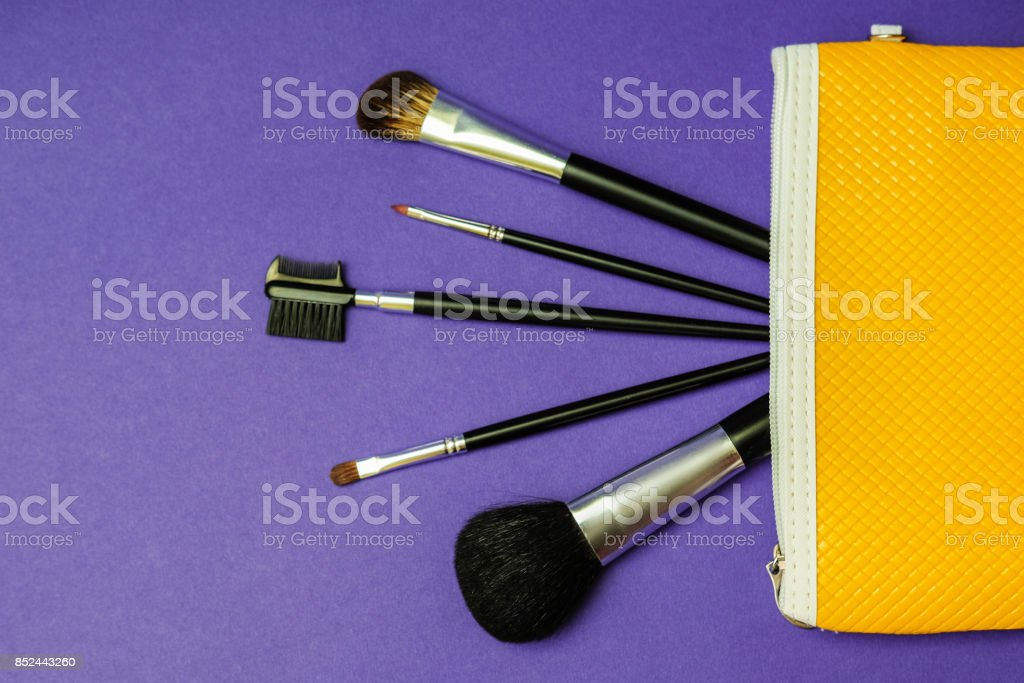 Make-up brushes in yellow cosmetic bag on a bright purple background. stock photo