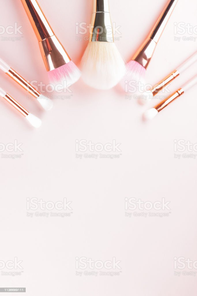 Makeup brushes on pink background. Set of golden makeup brushes,...