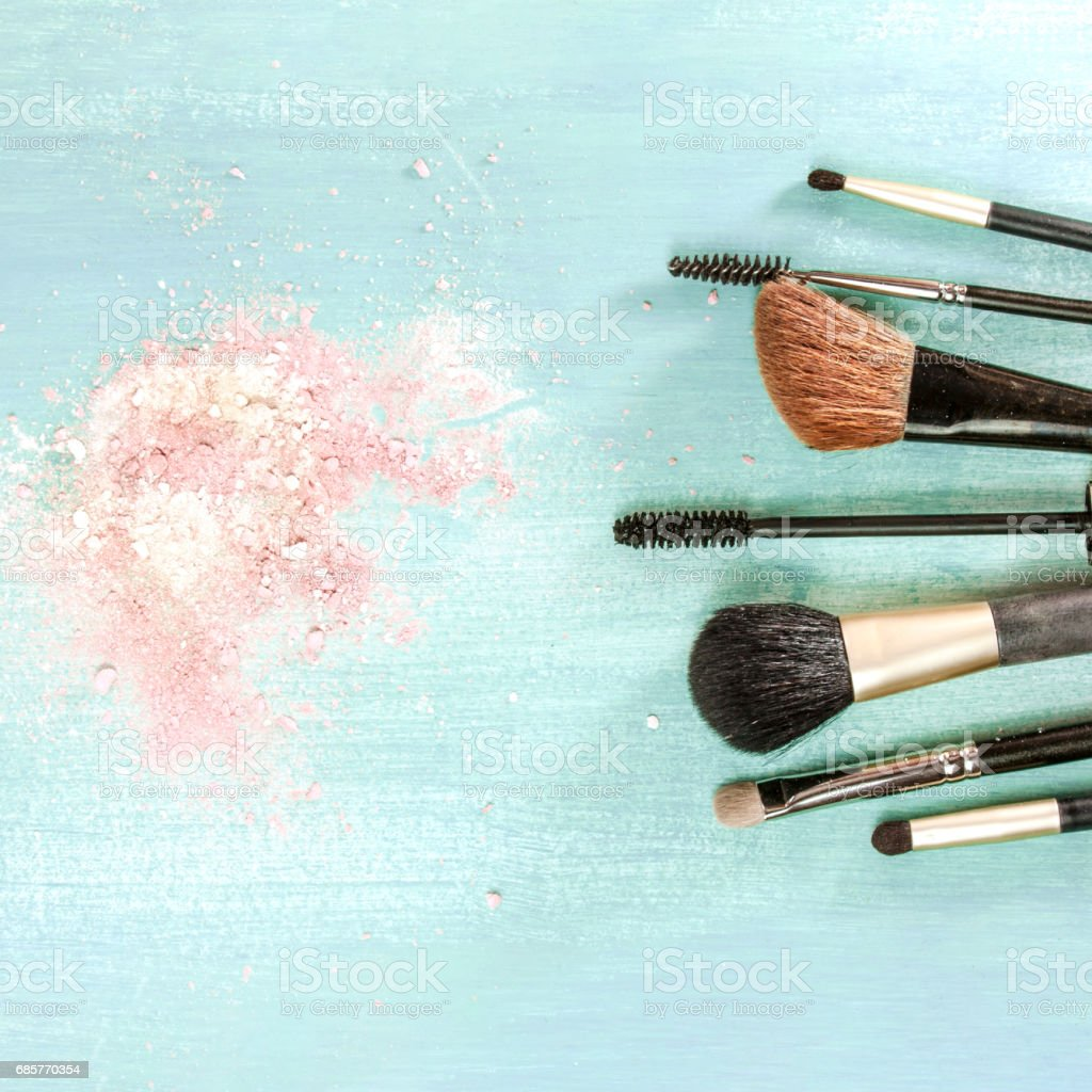 Makeup brushes on teal blue background, with traces of powder royalty-free stock photo