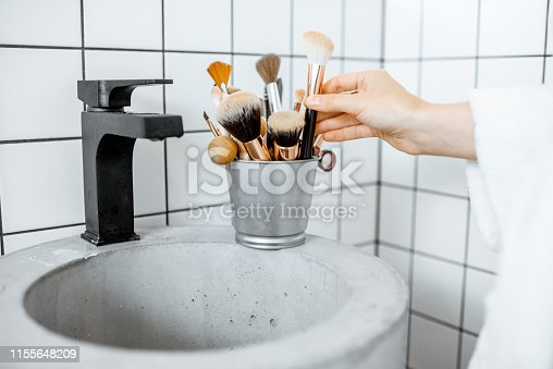 A bucket with makeup brushes on the modern sink in the bathroom