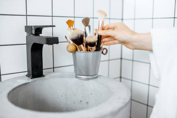 Makeup brushes on the sink in the bathroom A bucket with makeup brushes on the modern sink in the bathroom make up brush stock pictures, royalty-free photos & images