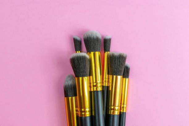 make-up bürsten pulver isoliert auf rosa mit kopierraum. schönheit m - rosa glitzer nägel stock-fotos und bilder
