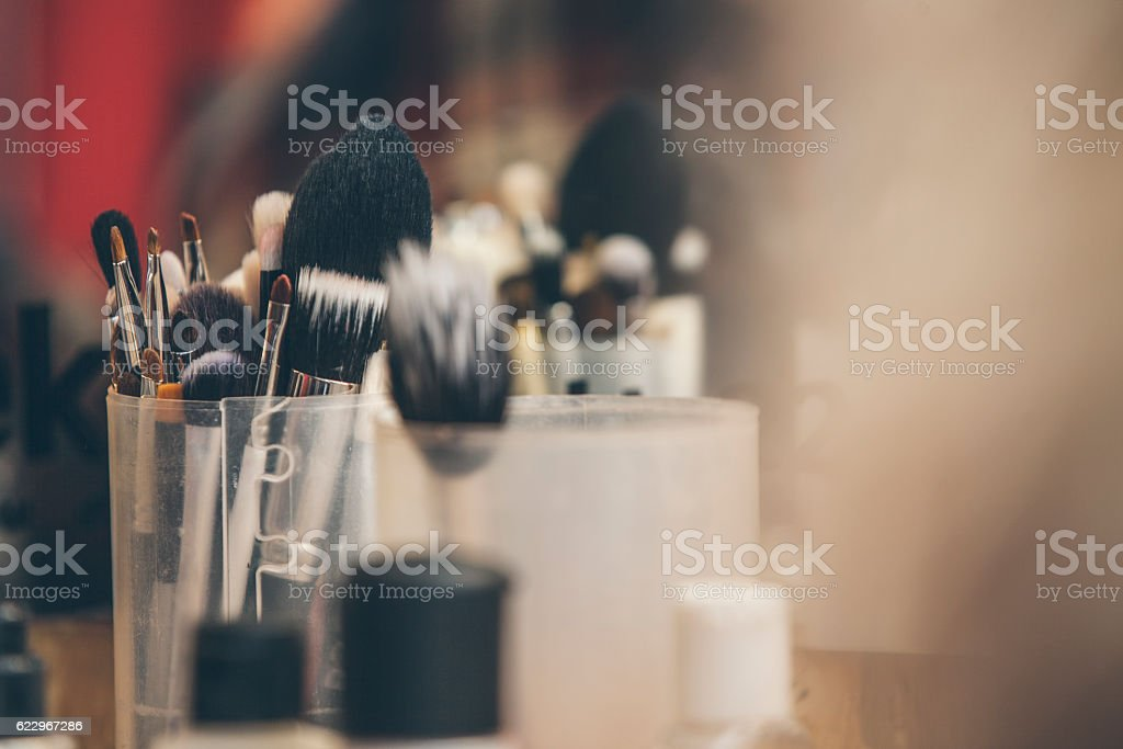 Makeup brushes stand in a transparent glass shot with blur stock photo
