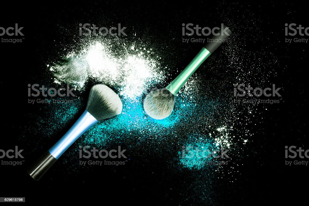 Make-up brushes with colorful powder on black background. – zdjęcie