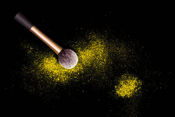Make-up brushes with colorful powder spilled glitter dust on black. – zdjęcie