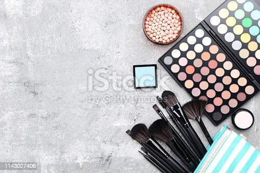 Makeup brushes with palette on gray background