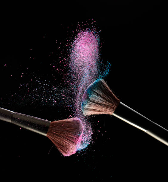 Make-up brushes with pink and blue powder explosion on black background stock photo