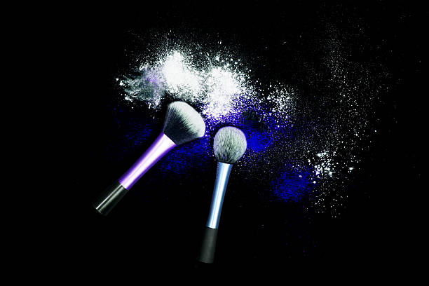 Makeup brushes with powder spilled glitter dust on black background. – zdjęcie