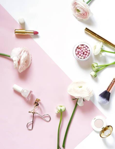 make-up kosmetik-accessoires-produkte-perle make-up puder und pinsel, lippenstift, rosa ranunkeln blumen auf weißem blass rosa hintergrund. flach zu legen. ansicht von oben. textfreiraum - blumen make up stock-fotos und bilder
