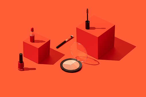 Makeup, cosmetics on red geometric background with red cubes