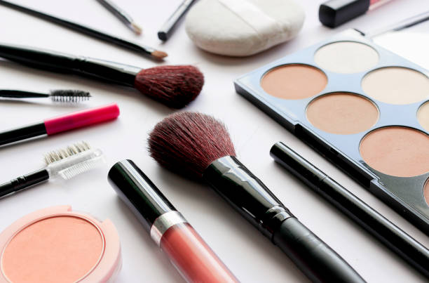 makeup cosmetics on white table with over light and soft-focus in the background – zdjęcie