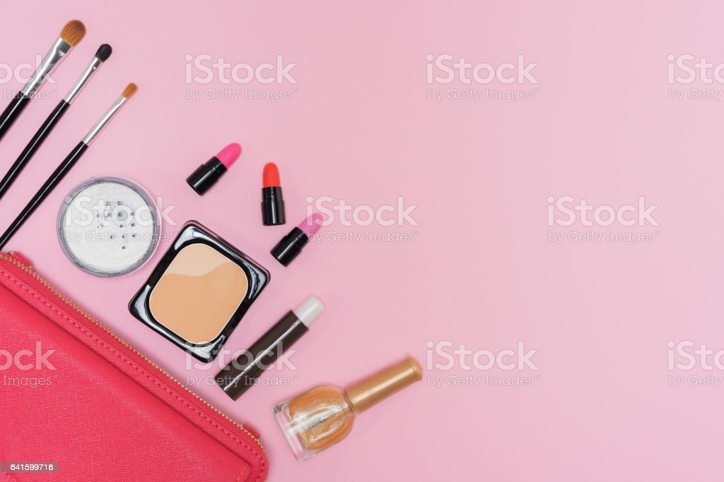 Makeup cosmetics palette and brushes on pink background flat lay stock photo