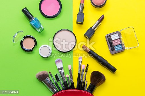 istock Makeup cosmetics tools background and beauty cosmetics, products and facial cosmetics package lipstick, eyeshadow on the green and yellow background. Lifestyle Concept 871034374