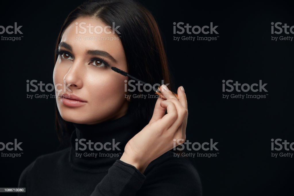 Makeup Cosmetics. Woman With Beauty Face Applying Black Mascara On...