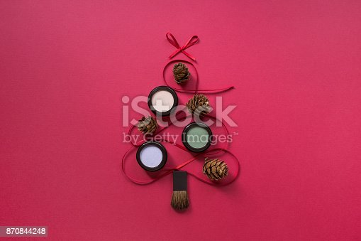 istock Makeup eyeshadow flat lay on red background, Christmas tree shape 870844248