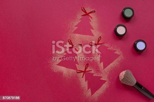 istock Makeup eyeshadow flat lay on red background, Christmas tree shape 870879188