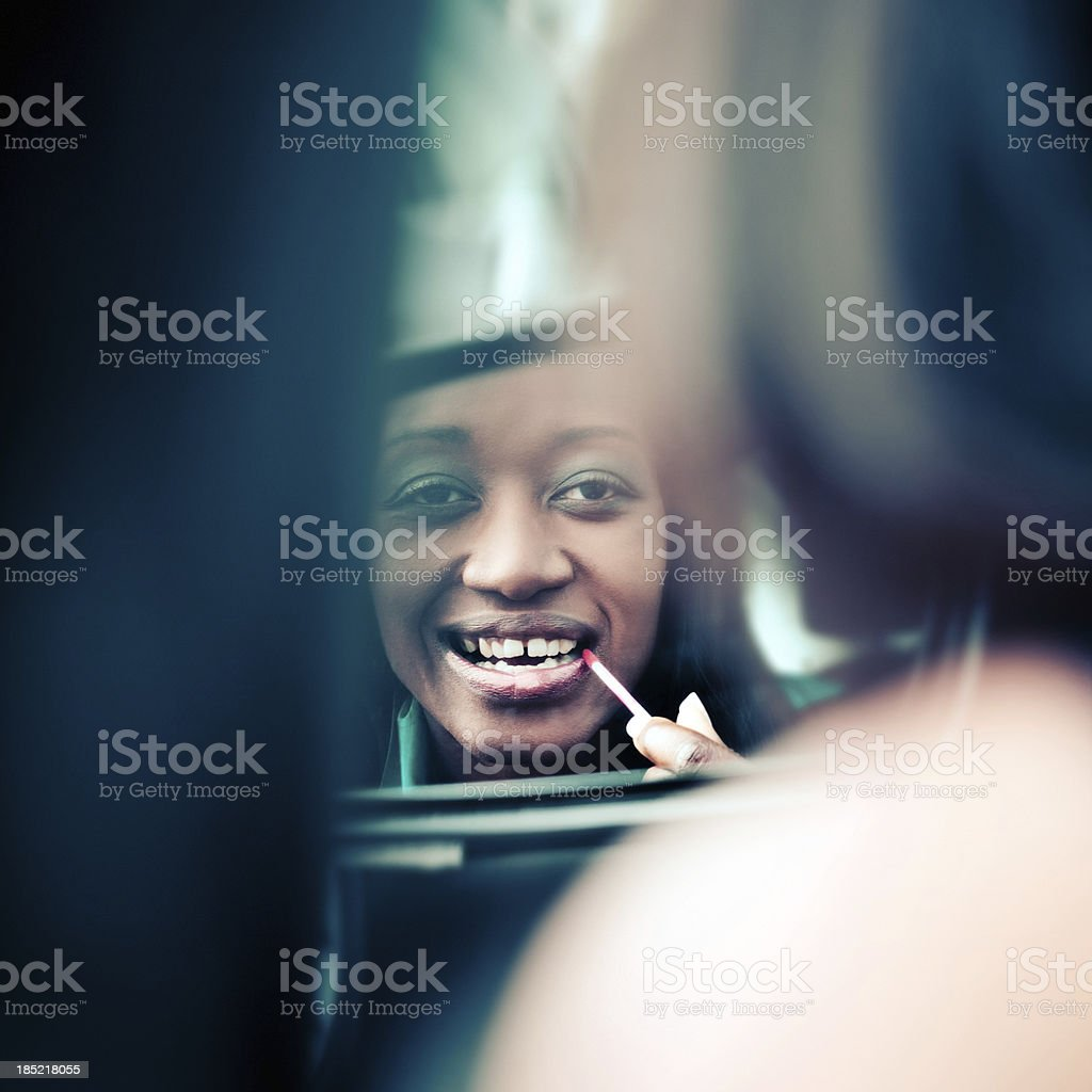 Make-up in the car Beautiful african woman looking in a side view car mirror and applying lip gloss.  Adult Stock Photo